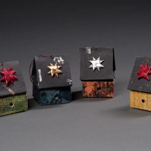 Image is of four small, colorful ornaments made from handmade paper to look like tiny birdhouses.